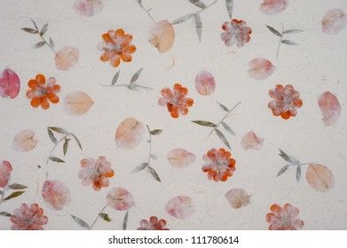 Sheet of handmade rice paper showing the natural elements used to make the paper including red flowers and green leaves.