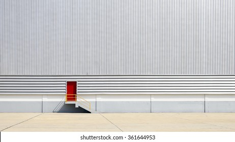 The sheet metal factory wall with the red  entrance door in the industrial park.The red door of the factory building.
