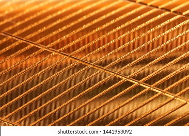 Sheet metal with a golden shade and diagonal notches. Background and pattern. Daylight.
