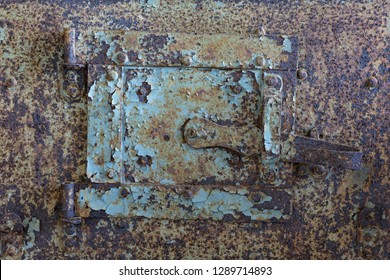 Sheet metal hatch for cleaning soot. Old rusty door with old layers of paint.