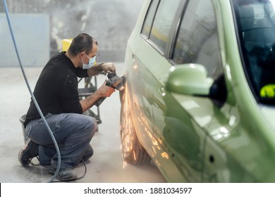 The sheet metal mechanic working in the workshop sanding a car with radial