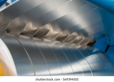 Sheet metal strips exiting the slitting line divided by circular metal plates