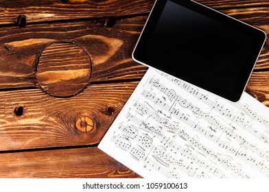 Sheet music and tablet on the table. Working place of the modern composer.