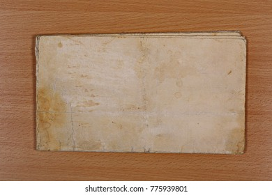 sheet of old, soiled paper on plywood background