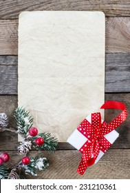 Sheet of paper with Christmas present and holly on wooden background
