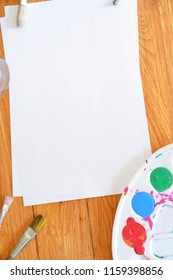 A sheet of paper with colors in a color palette and many brushes as well as brush water on a wooden background