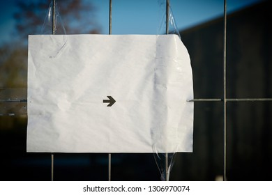Sheet of paper with a directional arrow on a fence