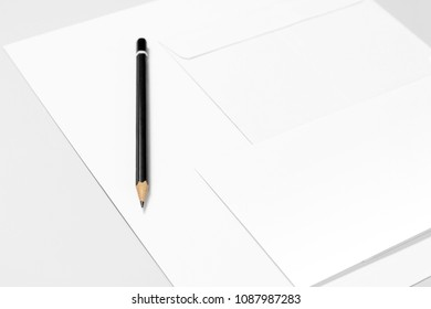 Sheet of paper, envelopes, and pencil over grey background
