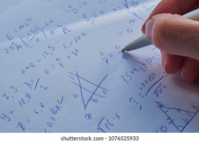 sheet of paper filled with calculations as a background. Math problems on graph with pencil. Doing algebra some school