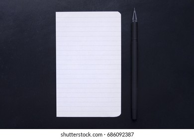 A sheet of paper and pen on a black background. Pen with a blank notebook on a black background. Back to school, the classic strict style. Business concept, Paper for notes. Office chancery