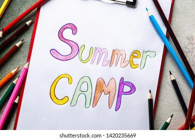 Sheet of paper with text SUMMER CAMP and pencils on grey background