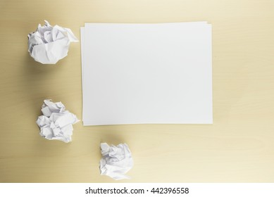 Sheet paper and three crumpled paper balls on the wooden table background, top view