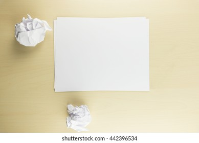 Sheet paper and two crumpled paper balls on the wooden table background, top view