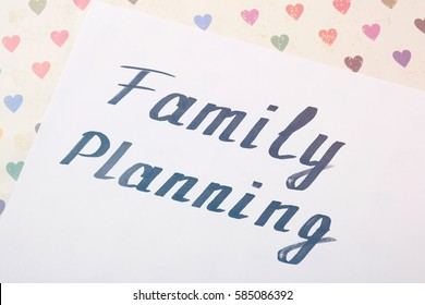 Sheet of paper with words FAMILY PLANNING, closeup