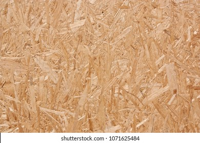 Sheet of plywood with fragments of compressed sawdust.