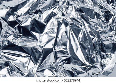 sheet of silver leaf aluminum foil background with shiny crumpled uneven surface