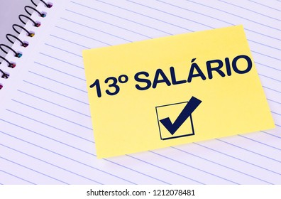 Sheet of yellow post note paper or self-adhesive notes written 13º salary (in portuguese)with background notebook.