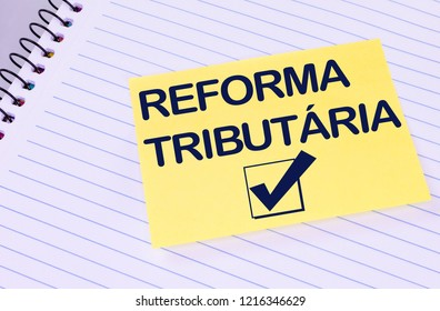 Sheet of yellow post note paper or self-adhesive notes written Tax Reform (in portuguese)with background notebook.