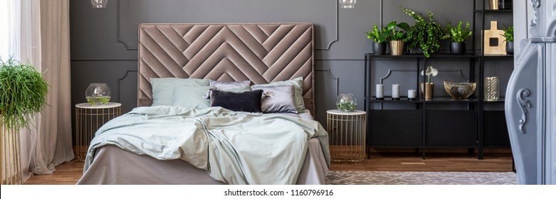 Sheets on bed with bedhead in grey and gold bedroom interior with plants. Real photo