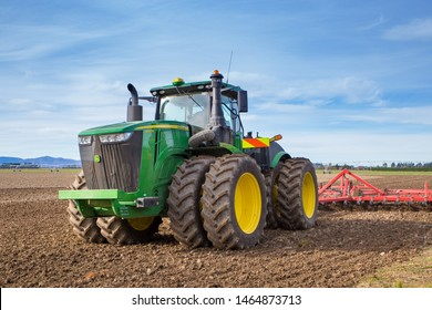 Sheffield, Canterbury, New Zealand, July 27 2019: A large modern John Deere tractor tows a cultivator in a field in winter