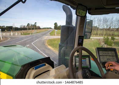 Sheffield, Canterbury, New Zealand, July 27 2019: A farmer drives a large modern John Deere tractor to a farm field on country roads