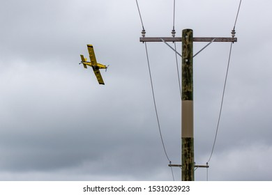 Sheffield, Canterbury, New Zealand, October 14 2019: A yellow crop duster, or top dressing plane, passes low over power lines as it spreads fertiliser over crops in a farm field