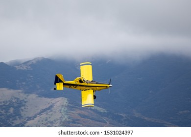 Sheffield, Canterbury, New Zealand, October 14 2019: A yellow crop duster, or top dressing plane, spreads fertiliser over crops in a farm field