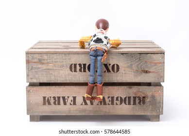 SHEFFIELD, UK - FEBRUARY 11, 2017: A Sheriff Woody toy character from Toy Story climbs on a wooden crate.