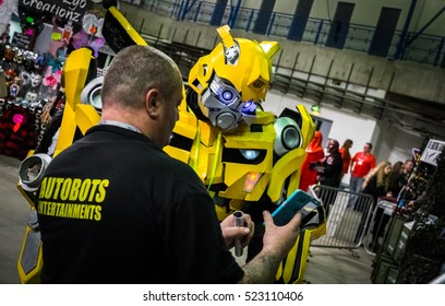 Sheffield, UK - June 12, 2016:  Cosplayer dressed as 'Bumblebee' from 'Transformers' being shown his photo on a mobile phone at the Yorkshire Cosplay Convention at Sheffield Arena