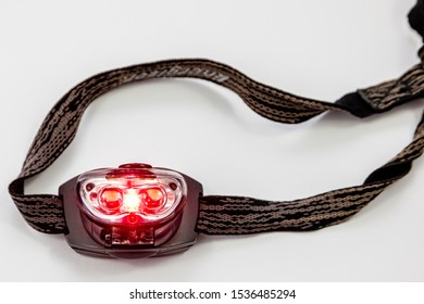 SHEFFIELD, UK – OCTOBER 12, 2019: A red light LED head torch for night reading, to limit blue light, to help night vision in camping, astronomy