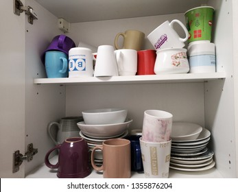 SHEFFIELD, UNITED KINGDOM, 1st April 2019: Assorted cups mugs and dishes in an office kitchen cupboard for use