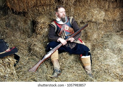 Sheffield Yorkshire England 1991. An unidentified reenactor of the English Civil War sits on hay wearing the period clothing of a Royalist Musketeer at a re-enactment of the Battle of Marston Moor.