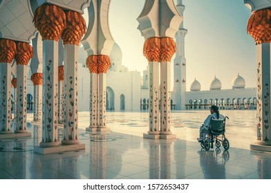 Sheikh Zayed Mosque. A disabled man is sitting in a wheelchair. A man prays in a mosque. Abu Dhabi. Summer 2016.