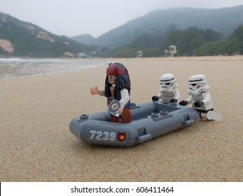 Shek O Beach, Hong Kong: 10 Mar 2017 - Lego Stormtroopers pushing Jack Sparrow's boat toward the sea. These mini figures are from Star Wars and Pirates of the Caribbean sets. Lego is a brick brand.