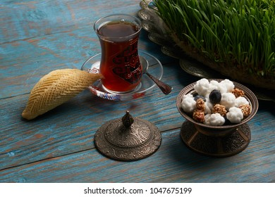 Shekerbura with glass of tea and sweet snack on wooden table with wheat grass semeni, dessert for Novruz holiday
