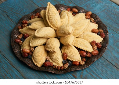 Shekerbura with nuts and honey on wooden table  background. Delicious dessert for Azerbaijan national holiday Novruz tray