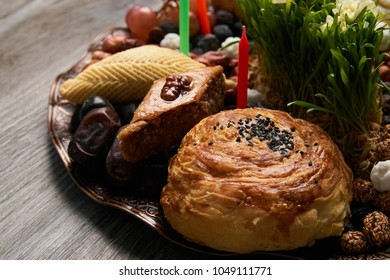 Shekerbura, pakhlava and gogal pastry, with dry fruits on novruz tray with semeni,  Azerbaijan national spring holiday close-up