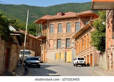 Sheki, Azerbaijan - August 13, 2017. Street view in Sheki, Azerbaijan, with historic brick buildings with tiled roofs and cars.