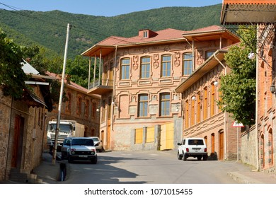 Sheki, Azerbaijan - August 13, 2018. Street view in Sheki, Azerbaijan, with historic brick buildings with tiled roofs and cars.