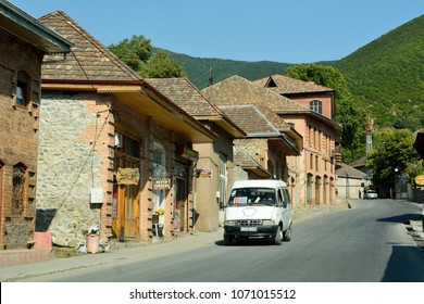 Sheki, Azerbaijan - August 13, 2018. Street view in Sheki, Azerbaijan, with historic brick buildings with tiled roofs, commercial properties and car.