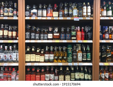 Shelf with an alcohol in a store. Large assortment of alcoholic beverages: KHARKIV, UKRAINE - 11 February, 2021.