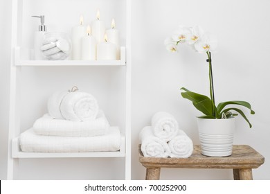 Shelf with clean towels, candles, flowerpot on bathroom wooden table