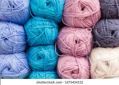 Shelf with a lot of color yarn for diy knitting. Selection of colorful yarn wool on shopfront. Knitting background. Knitting balls of wool, crochet hooks pattern.