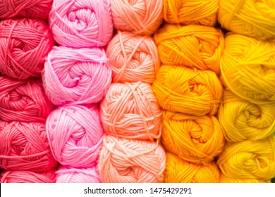 Shelf with a lot of color yarn for diy knitting. Selection of colorful yarn wool on shopfront. Knitting background. Knitting balls of wool, crochet hooks pattern. Orange, pink, yellow, lemon