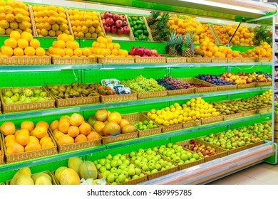 Shelf with fresh organic fruits on a farm market supermarket. Apple, orange, grapes, persimmon, kiwi, pineapple, pear, plum, prunes, melon, watermelon, exotic fruit. fruits, fruits, fruits, fruits.