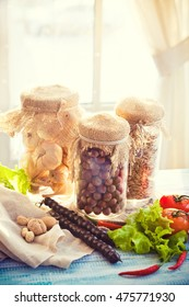 Shelf in kitchen with nuts jars and vegetable