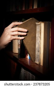shelf library, a female hand takes a book from the shelf