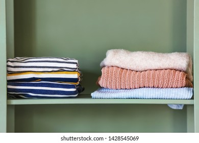 Shelf with stacks of clean clothes on color background