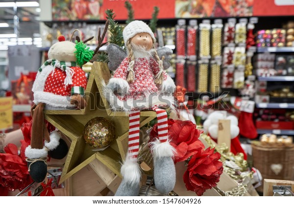 Shelf in a store with a clearance sale for Christmas or New Year 2020 in a store with decor. Stuffed toy girls and wooden stars on the background of shelves in the store