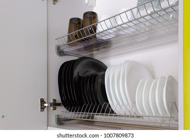 Shelf for tableware drying in a modern kitchen. Black and white plates and cups on metal rack inside kitchen cupboard